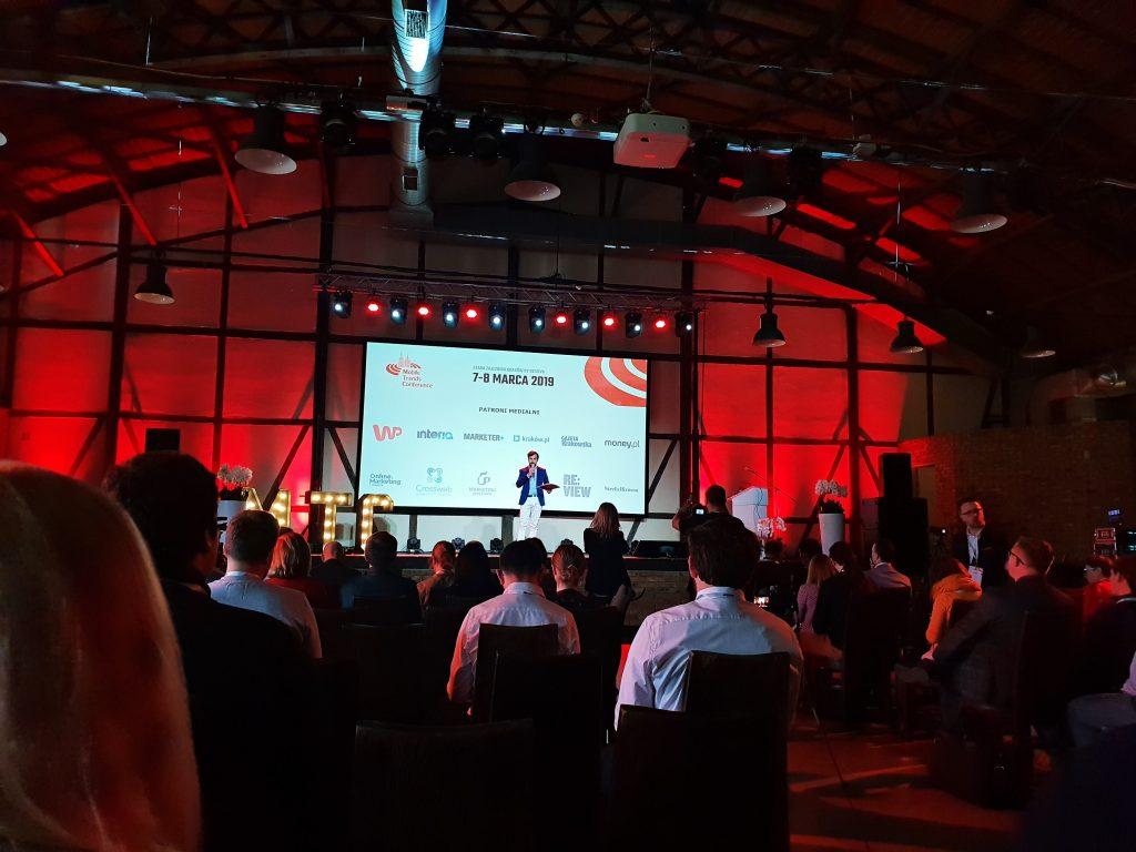 Mężczyzna z mikrofonem na scenie podczas konferencji