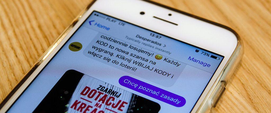 Widok ekranu telefonu. Chatbot rozmawia z klientem i proponuje udział w loterii.