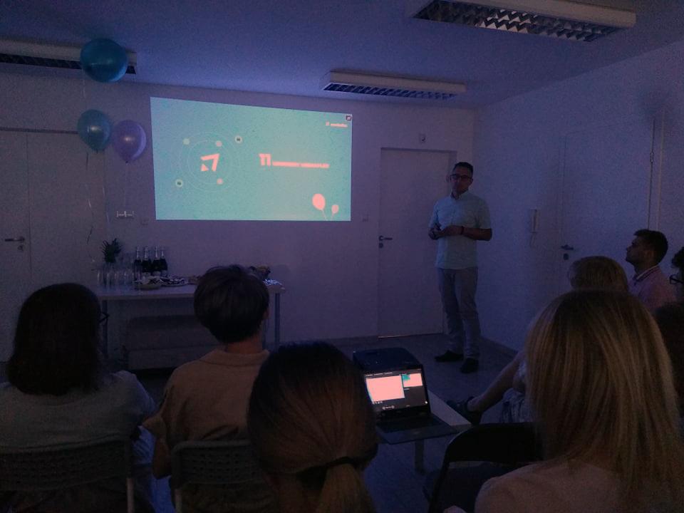 Na ścianie wyświetlona prezentacja firmy z okazji 11 urodzin. Dawid Kloch, prezes Mediaflex w trakcie wystąpienia, pozostali specjaliści IT siedzą na krzesłach zwróceni w jego stronę.