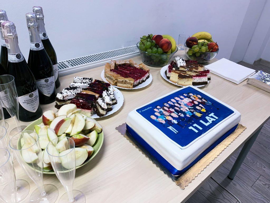 Nasi programiści uwielbiają kodować. Uwielbiają też słodkości. Na zdjęciu firmowy poczęstunek - na stole ciasta i owoce. Na dużym torcie widoczne karykatury wszystkich specjalistów IT, którzy pracują w Mediaflex.