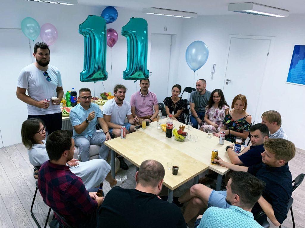 Ekipa specjalistów IT przy stole podczas urodzin firmy. Dwie osoby trzymają balony tworzące liczbę 11.
