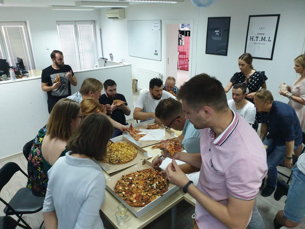 Specjaliści IT naszej firmy podczas jedzenia pizzy.