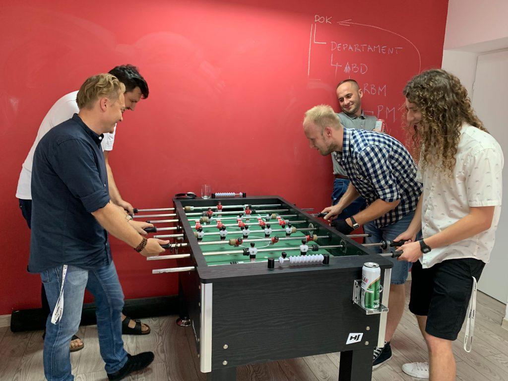 Nasi programiści aplikacji mobilnych i systemów podczas gry w piłkarzyki w jednym z pokojów w firmie.