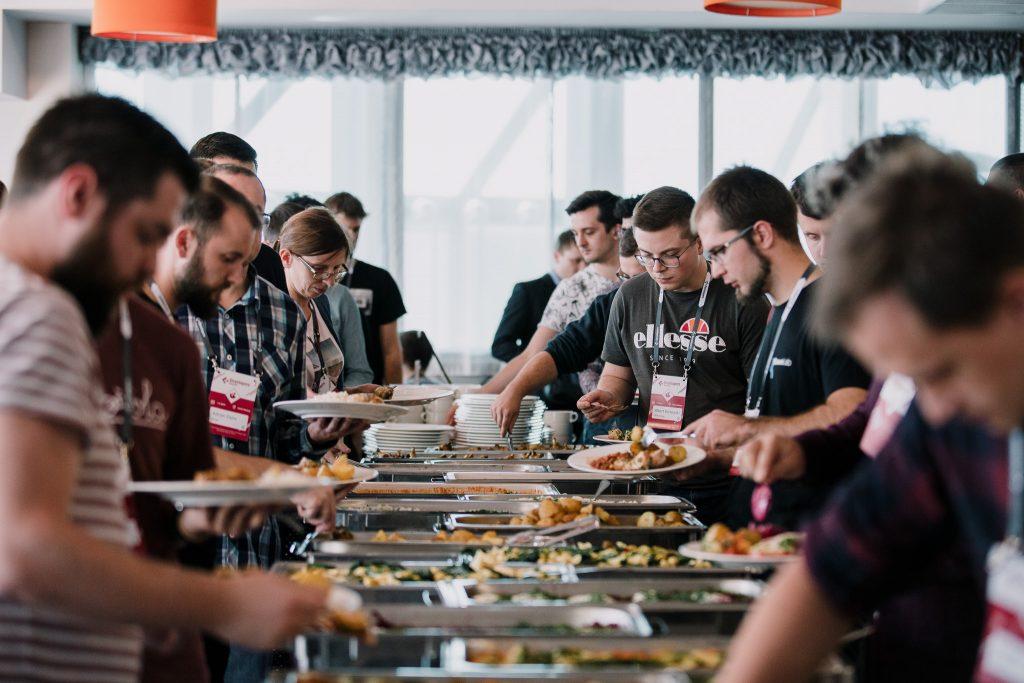 Uczestnicy konferencji podczas przerwy obiadowej. Po lewej stronie widoczny nasz UI/UX Designer i jeden z programistów