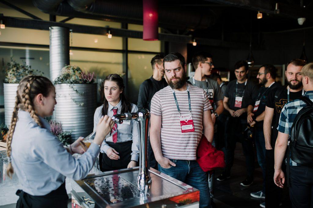Uczestnicy konferencji podczas przerwy. Na zdjęciu widoczni nasi dwaj programiści i jeden specjalista UI/UX Designer