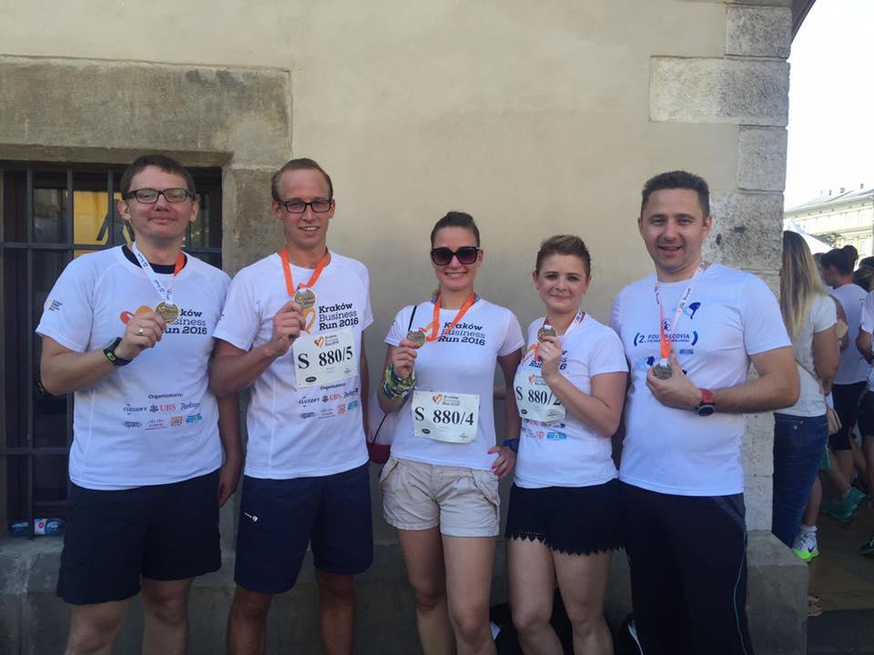 5 osób z firmy Mediaflex tuż po biegu w Kraków Business Run w 2016 roku. Wszyscy uczestnicy trzymają w ręku medale.