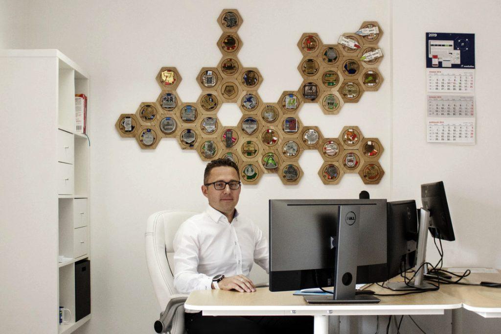 Dawid Kloch, prezes Mediaflex, w pracy brzy biurku przed monitorem, w tle na ścianie wiszą jego liczne medale z biegów i maratonów