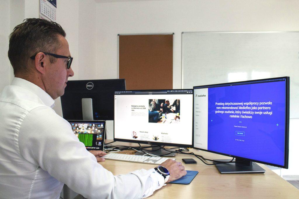 Dawid Kloch siedzący przy biurku w swojej firmie i przeglądający stronę Mediaflex.