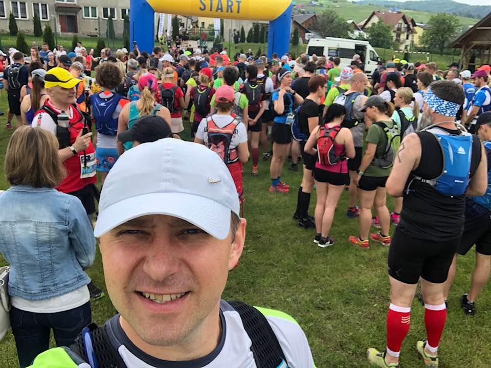 Dawid Kloch robiący sobie selfie przed biegiem. W tle inni uczestnicy biegu.
