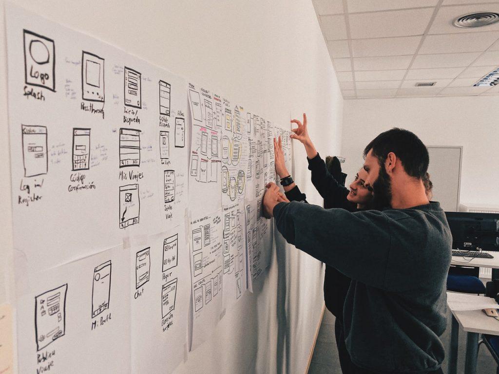 Zespół ludzi przy białej tablicy z rozpisanymi arkuszami projektowymi, planujących konkretne działania w projektach IT