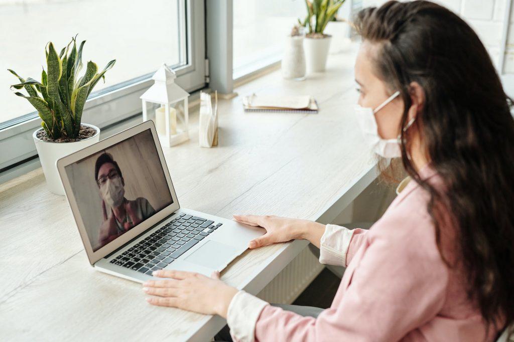 Rozmowa wideo kobiety i mężczyzny. Podczas wideokonferencji boje mają maseczki na twarzy, co może wskazywać, że chronią się przed koronawirusem.