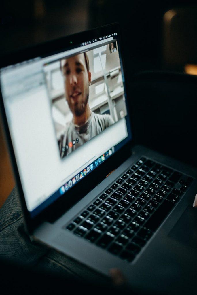 Zrzut ekranu laptopa, na którym widać chłopaka prowadzącego rozmowę online.