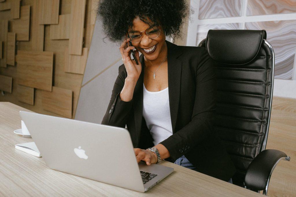 Uśmiechnięta kobieta, najprawdopodobniej managerka lub szefowa, pracująca przed laptopem i kontaktująca się z kimś przez telefon.
